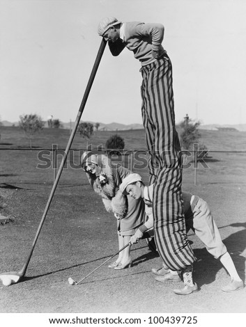 Golf game with man on stilts - stock photo