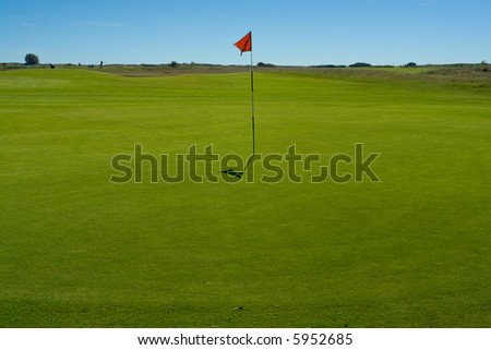 Golf green and flag at a seaside course - stock photo