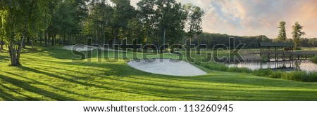 Golf green and traps with rays of sun - stock photo