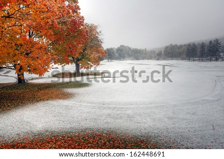 Golf green covered with snow during the fall. - stock photo
