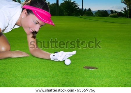 Golf green hole course woman humor flicking hand a ball inside in short putt - stock photo