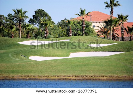 Golf green lake and bunker with house in background