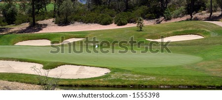 Golf Green with bunkers surrounding it - stock photo