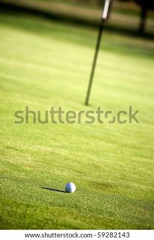 Golf green with one golf ball, shallow focus - stock photo