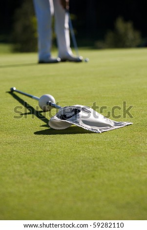 Golf green with white flag, shallow focus - stock photo