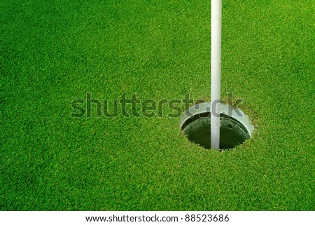 Golf hole and flag with the green grass - stock photo