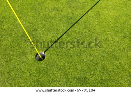 Golf hole in a green grass field background - stock photo