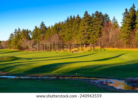 Golf hole shot from green back to tee across stream - stock photo