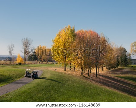Golf in fall with men driving carts to the fairway - stock photo