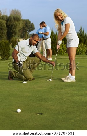 Golf instructor teaching pretty golfer to putt.