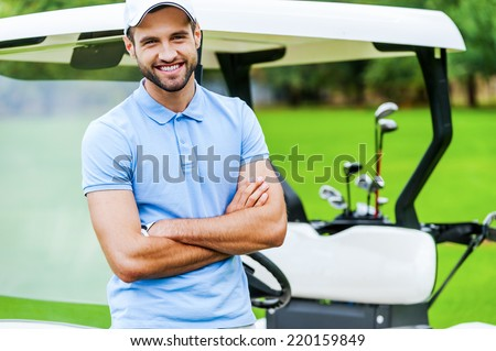 Golf is my favorite game! Handsome young man keeping arms crossed and smiling while leaning at the golf cart while standing on golf course - stock photo