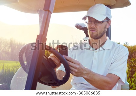 golf man relaxing on buggy cart with mobile cellphone summer vacation - stock photo