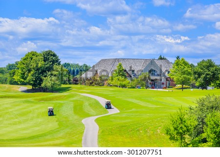 Golf place with gorgeous green and custom built luxury big house on background. - stock photo