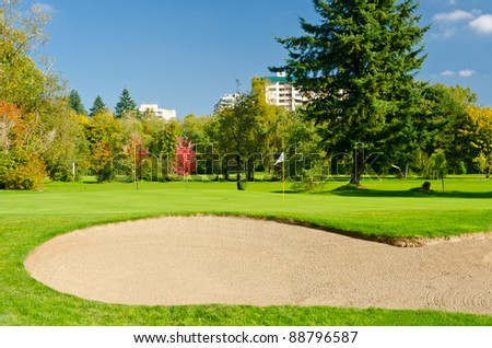Golf place with gorgeous green and nice forest and urban view. - stock photo