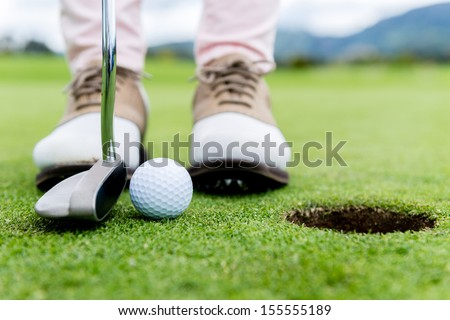 Golf player at the putting green hitting ball into a hole  - stock photo