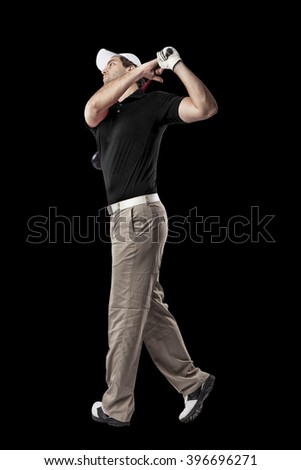 Golf Player in a black shirt taking a swing, on a black Background.