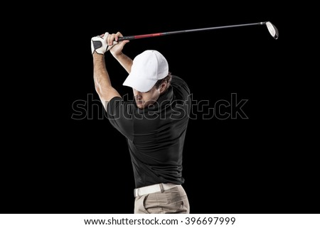 Golf Player in a black shirt taking a swing, on a black Background. - stock photo