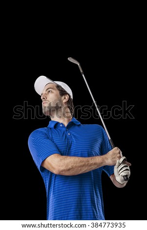 Golf Player in a blue shirt taking a swing, on a black Background.