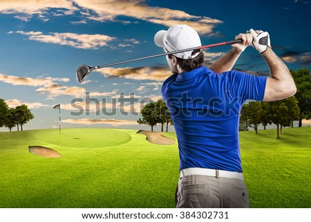 Golf Player in a blue shirt taking a swing, on a golf course. - stock photo