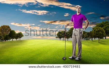 Golf Player in a pink shirt standing on a golf course.