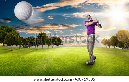 Golf Player in a pink shirt taking a swing, on a golf course. - stock photo