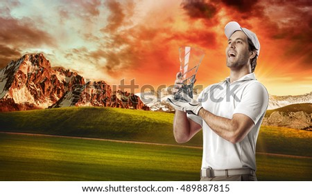Golf Player in a white shirt celebrating with a glass trophy in his hands, on a golf course.
