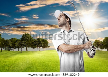 Golf Player in a white shirt taking a swing, on a golf course.