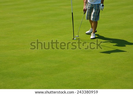 Golf player on a green course and hole - stock photo