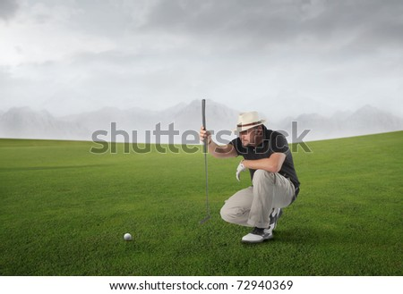 Golf player on a green meadow observing a golf ball - stock photo