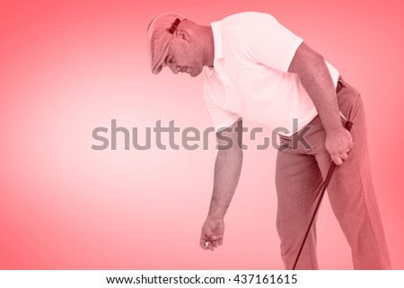 Golf player picking up golf ball against red vignette