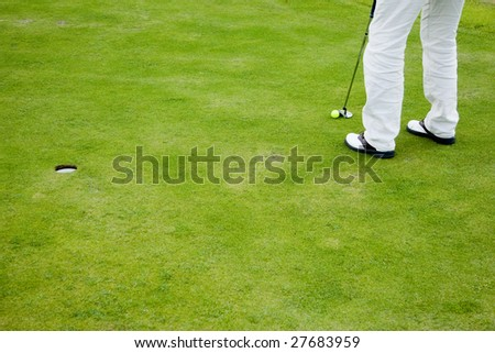 Golf player practicing on putting green - stock photo