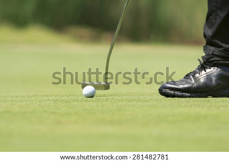 Golf player putting on the green - stock photo