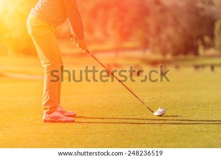 Golf player tee off at sunset with sunlight sunburst - stock photo