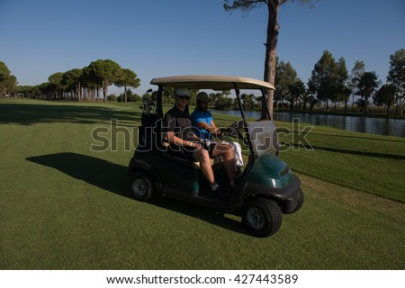 golf players driving cart at course on beautiful morning sunrise. friends together have fun and relax on vacation. - stock photo