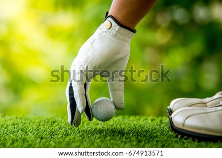 golf players hand placing ball on grass