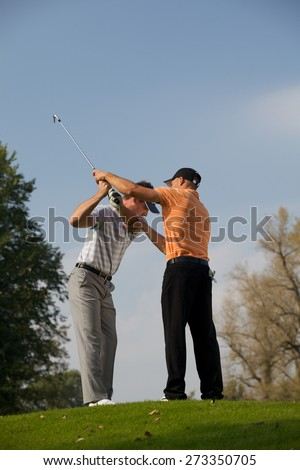 Golf professional helping young man with his swing - stock photo