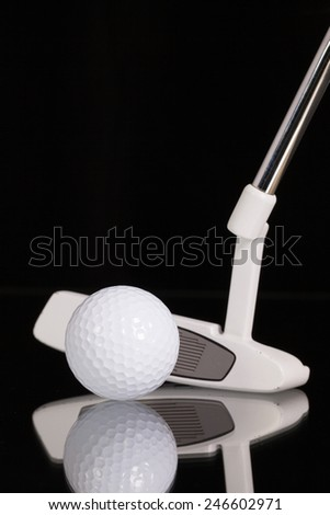 Golf putter and different golf equipments on the black glass desk - stock photo