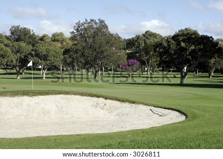 Golf Putting Green With Flag And Sand Bunker In The Foreground - stock photo