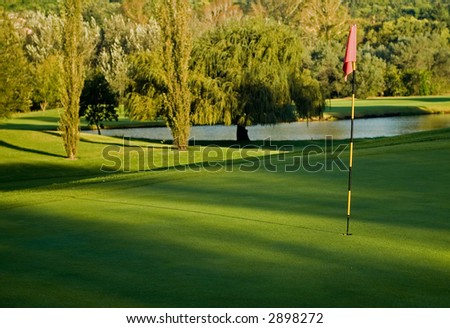 Golf putting green with flag and water hazard pond background - stock photo