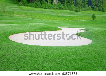 Golf: sand trap on the green grass - stock photo