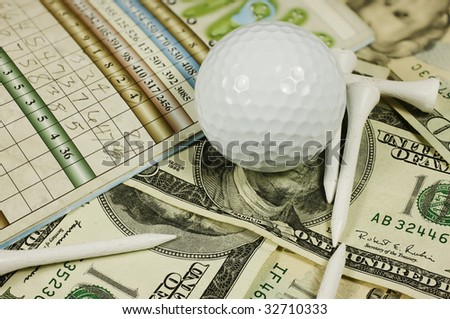 Golf scorecard with ball and tees over a bed of cash. - stock photo