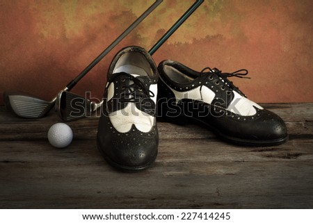 Golf shoes with golf clubs on grunge background - stock photo