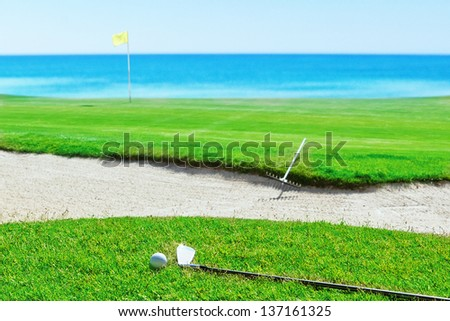 Golf stick and ball on grass against the sea. Rake near the sand. - stock photo