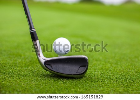 Golf stick and ball on green grass - stock photo