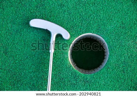 Golf stick near the hole - stock photo