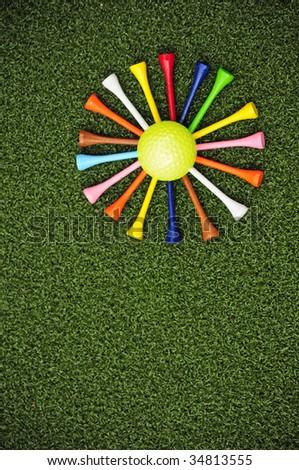 golf tees arranged around golf ball to form daisy - stock photo