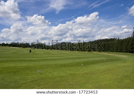 golf trolley standing on fairway of a beautiful golf course with dramatic summer sky - stock photo