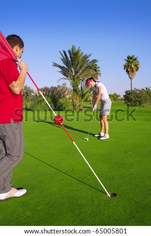 golf woman player putting golf ball and man holds flag - stock photo