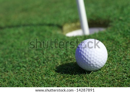 Golfball in front of the hole - stock photo