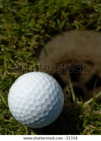 Golfball laying on the edge of a hole. Narrow DOF, focus on the ball. - stock photo